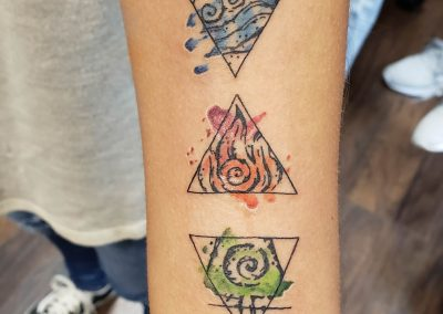 four colored tattoo triangles