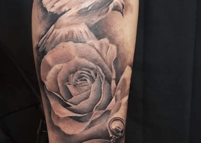 clock, rose, dove tattoo on arm