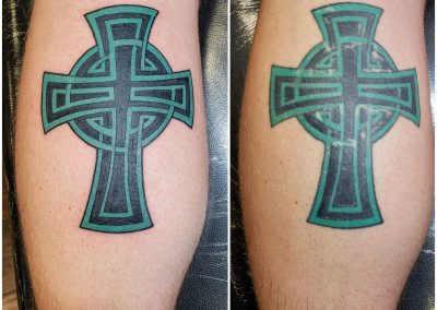 green and black tatto of cross